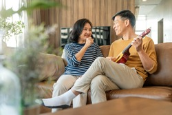 sweet Asian senior Couple sing play acoustic ukulele instrument. Happy Smiling Elderly grandparent having fun and enjoying their Retirement life. Lifestyle, Party happy lifestyle