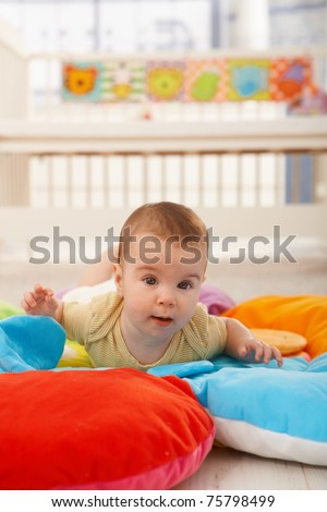 Sweet baby crawling on colorful playmat.?
