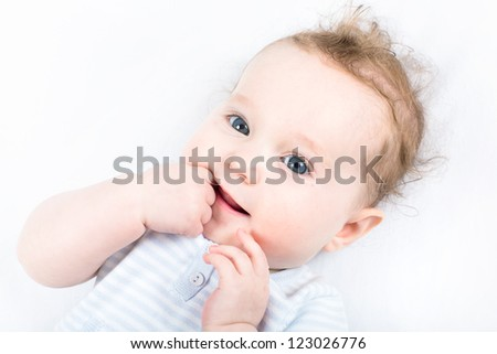 Sweet baby girl in a blue knitted dress sucking on her finger