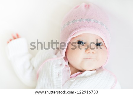 Stock Photo Sweet baby girl in a pink knitted hat