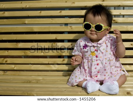 sweet baby girl sitting on a the porch wearing sunglasses