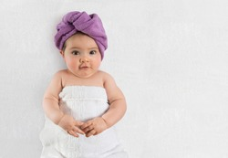 Sweet baby girl wrapped in white towel and purple bath turban