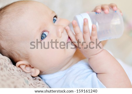 sweet baby holding bottle and drinking water
