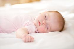 sweet baby infant girl sleeping on her bed