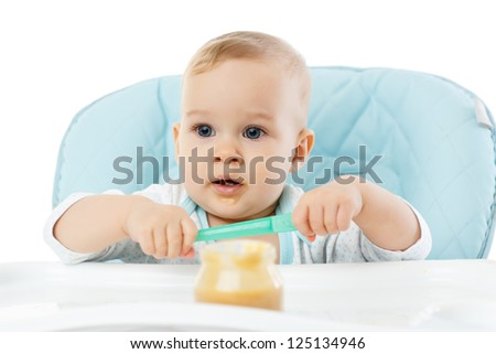Sweet baby learning to eat with spoon sits on baby chair on a white background.