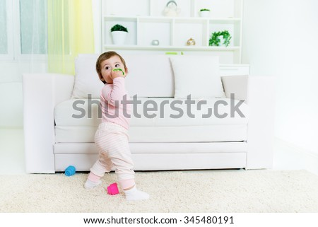 Sweet baby little girl standing in front of the sofa, holding baby toy.Living room interior.Shallow doff, copy space