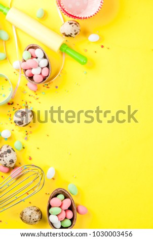 Sweet baking concept for Easter, cooking background with baking - with a rolling pin, whisk for whipping, cookie cutters, quail eggs, sugar sprinkling. Bright yellow background, copy space top view #1030003456