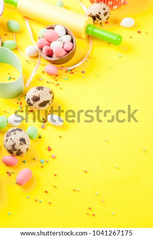 Sweet baking concept for Easter, cooking background with baking - with a rolling pin, whisk for whipping, cookie cutters, quail eggs, sugar sprinkling. Bright yellow background, copy space #1041267175