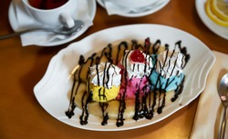Sweet banana split, American ice cream based dessert with whipped cream topped with chocolate sauce garnished with maraschino cocktail cherry.