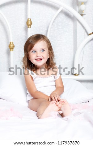 Sweet barefoot toddler girl in bed