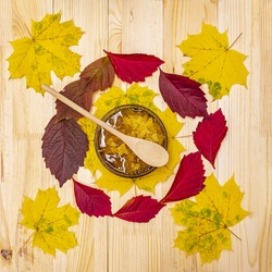 Sweet Bashkir honey on a wooden table decorated with autumn leaves served in a bowl with a wooden spoon