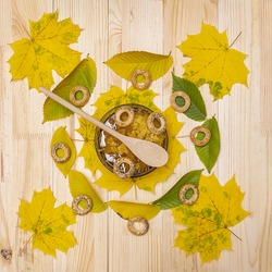 Sweet Bashkir honey on a wooden table decorated with leaves served in a bowl with a wooden spoon and bagels