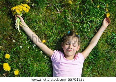 Sweet beautiful girl lying on a green meadow with dandelions
