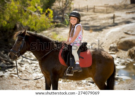 sweet beautiful young girl 7 or 8 years old riding pony horse hugging and smiling happy wearing safety jockey helmet posing outdoors on countryside in summer holiday