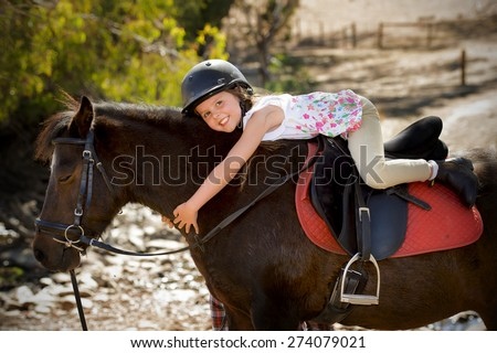 sweet beautiful young girl 7 or 8 years old riding pony horse hugging happy in  safety jockey helmet posing outdoors on countryside on summer holiday in love animal concept
