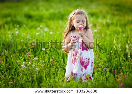 Sweet blonde little girl smelling field flowers on the meadow