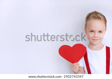 Sweet boy with a heart in his hand in a white T-shirt. With copy space Foto stock ©