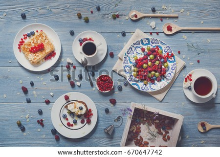 Sweet breakfast. Baked pea and pie dessert with red currant, raspberry and bluberries. Beautiful food served at blue rustic wooden table on white porcelain plates, tea and coffee cups. Top view #670647742