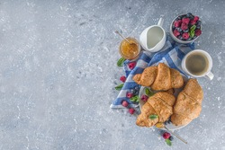 Sweet breakfast butter croissants with coffee cup, orange jam and fresh summer berries. Traditional continental breakfast with croissants concept, grey stone background copy space