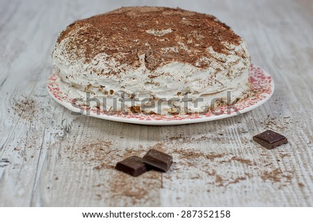 sweet brownie chocolate cream cake topped with black chocolate and cream with chocolate on wooden background