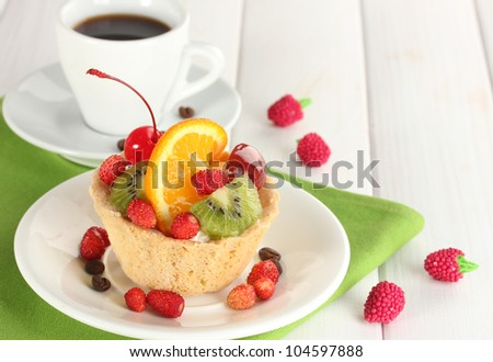 sweet cake with fruits on plate and cup of coffee on wooden table