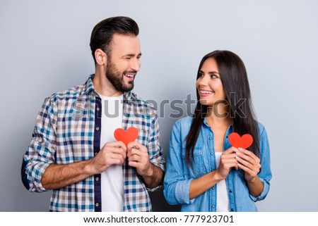 Sweet, cheerful, positive, smiling couple in shirts holding small red paper hearts in hands, having best date, looking to each other over grey background