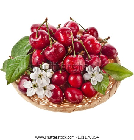 Sweet cherries with flowers in basket isolated on white background - stock photo