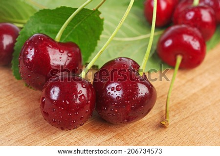 Sweet cherries with water drops on wooden table