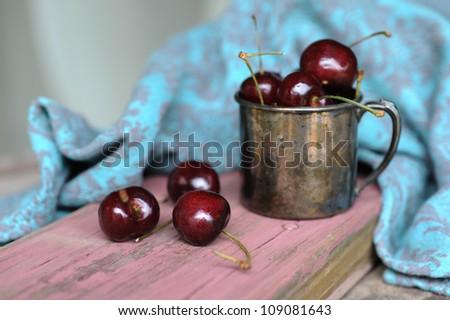 Sweet cherry and Tin ancient mug on the garden