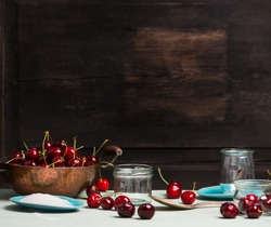 Sweet cherry jam and  jelly preserve preparing on rustic wooden background, place for text, kitchen scene