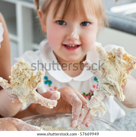 Sweet child baking cookies with hands in the kitchen