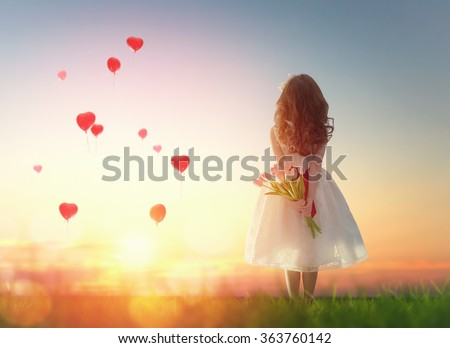 Stock Photo Sweet child girl looking at red balloons. Little child girl holding bouquet of flowers. Balloons in shape of heart flying in the sunset sky. Wedding, Valentine, love concept.