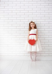 Sweet child girl with red heart. Happy little girl with Valentine's gift at a blank brick wall. Wedding, Valentine concept.
