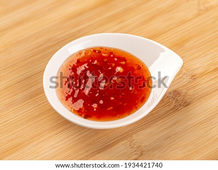 Sweet chilli sauce in small white bowl on bamboo board Photo stock ©