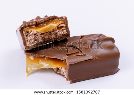 Sweet chocolate bar with milk-cream and caramel fillings. Chocolate bar broken into two pieces. Close-up. ストックフォト ©