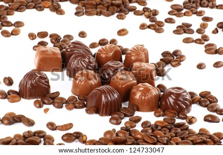 sweet chocolate candies and coffee beans isolated on white background