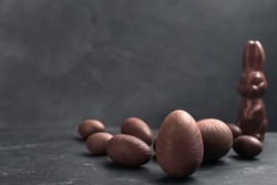 Sweet chocolate eggs and bunny on black table. Space for text
