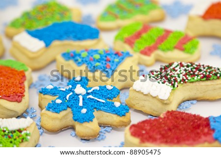 sweet christmas cookies decorating with icing and sprinkles on a white background