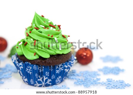 sweet christmas cupcake decorating with icing , sprinkles and candy on a white background - stock photo