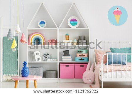 Sweet colorful decorations and white furniture in a fun kid's bedroom interior with a pastel pink rabbit pillow #1121962922