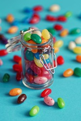 sweet colorful jelly beans in a jar, blue background