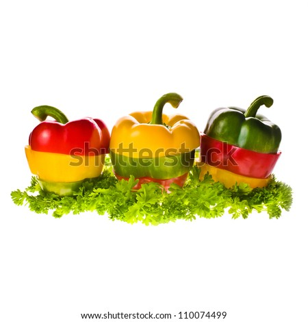 Sweet colorful paprika , red, yellow, green cut into rings  on parsley leaves isolated on white