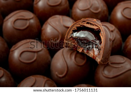 Sweet confectionery and candy indulgence concept theme with close up on a bitten cherry filled chocolate praline on top of many other delicious pralines with copy space