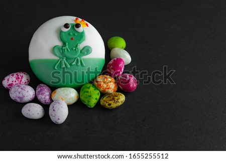 Sweet confectionery in the form of figures of funny animals on a dark background. Multi-colored sweets are scattered next to the icing.