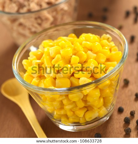Sweet corn grains and tuna in glass bowls with black pepper corns and wooden spoon on the side (Selective Focus, Focus one third into the corn)