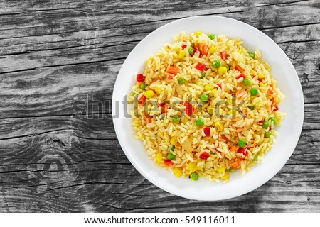 Sweet Corn, red bell pepper, green peas delicious  healthy Risotto on white plate on old wooden table, view from above #549116011