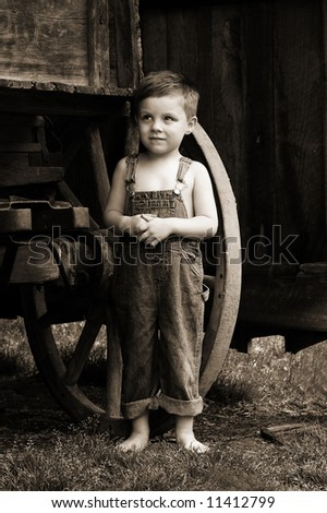 Sweet country boy next to a wagon wheel with an antique vintage feel
