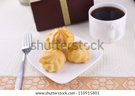 Sweet cream cake dessert with black hot cup of coffee and little gift on the table