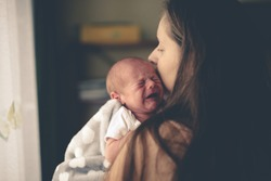 Sweet crying newborn baby at mom on hands, concept real interior, natural lifestyle photo