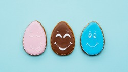 Sweet decoration. Kids ornament. Bakery food art. Creative dessert for boy and girl. Tree cute pink blue chocolate happy smile face egg shape gingerbread cookie isolated on light background.